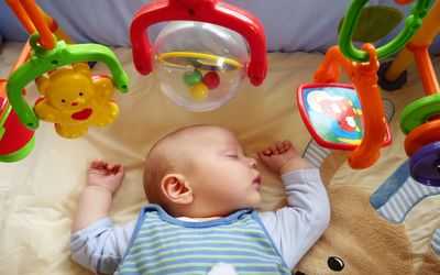 Baby boy sleeps peacefully on playmat