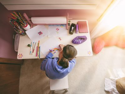 little girl drawing at a desk