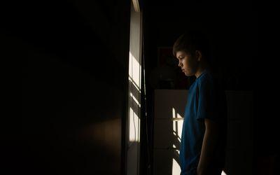 Sad teen in room.