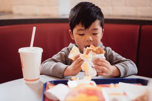 A boy eating at a fast food restaurant