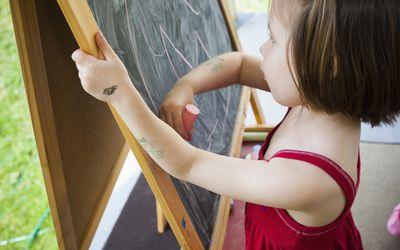 little girl drawing on chalk board easel
