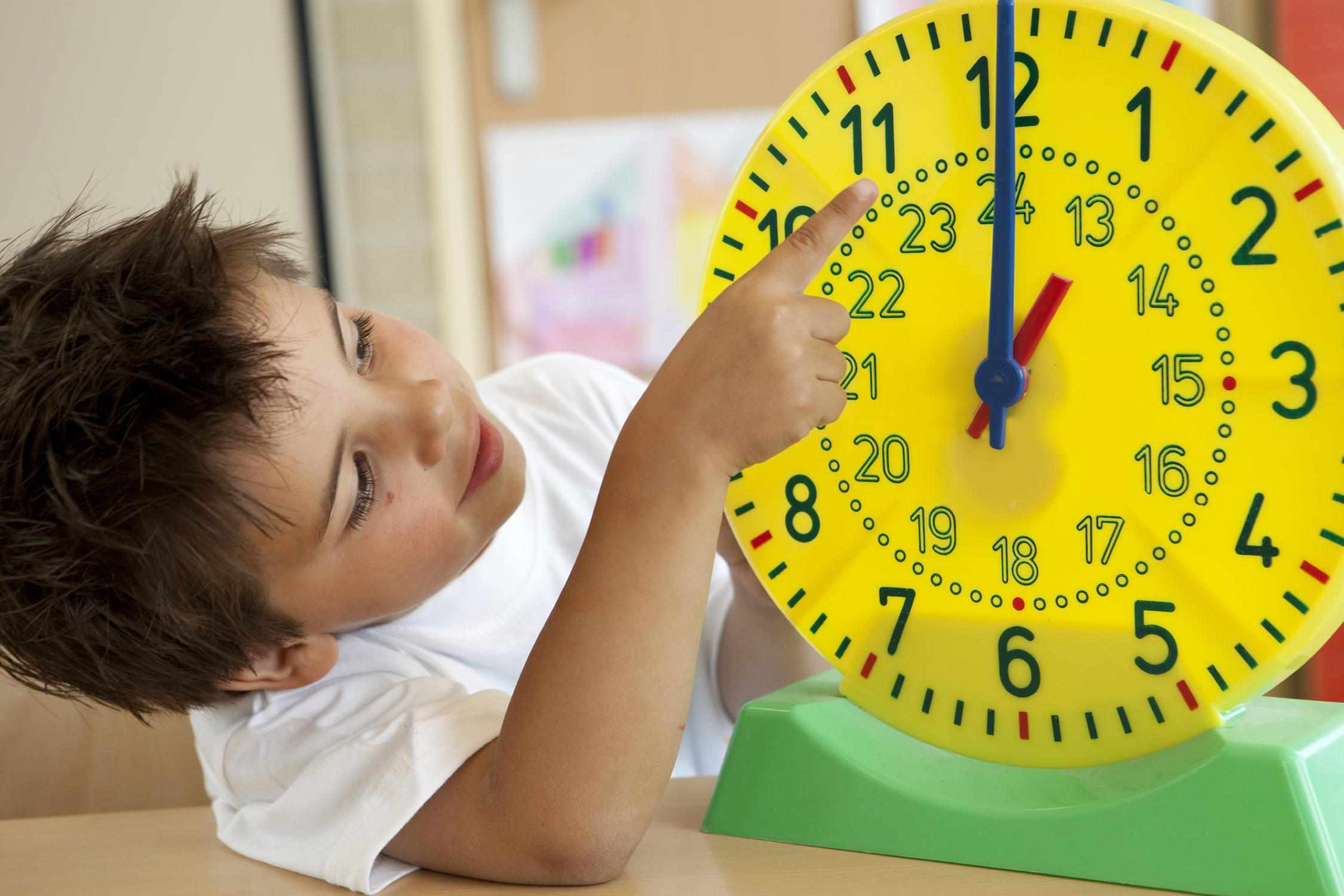 little boy pointing to a clock