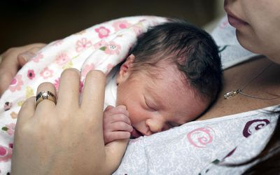 'Newborn premature baby girl, just two days old, resting on her mother's breast.'