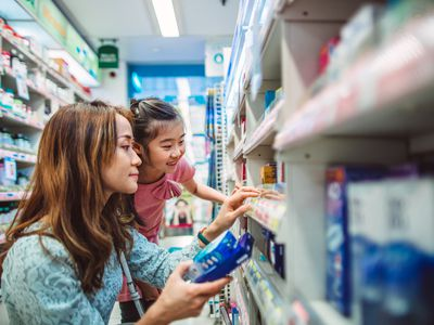 Asian woman and child crouching down at the drugstore examining medicine.