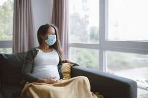 A pregnant person sits on a couch with a face mask on and a blanket while staring out the window.