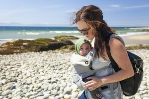 Mother with baby son in carrier at beach