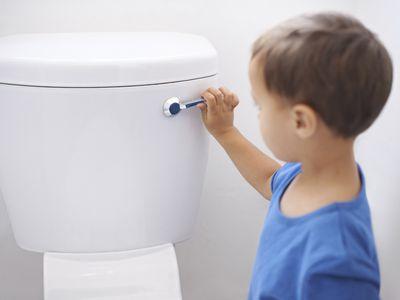 A young boy flushing a toilet