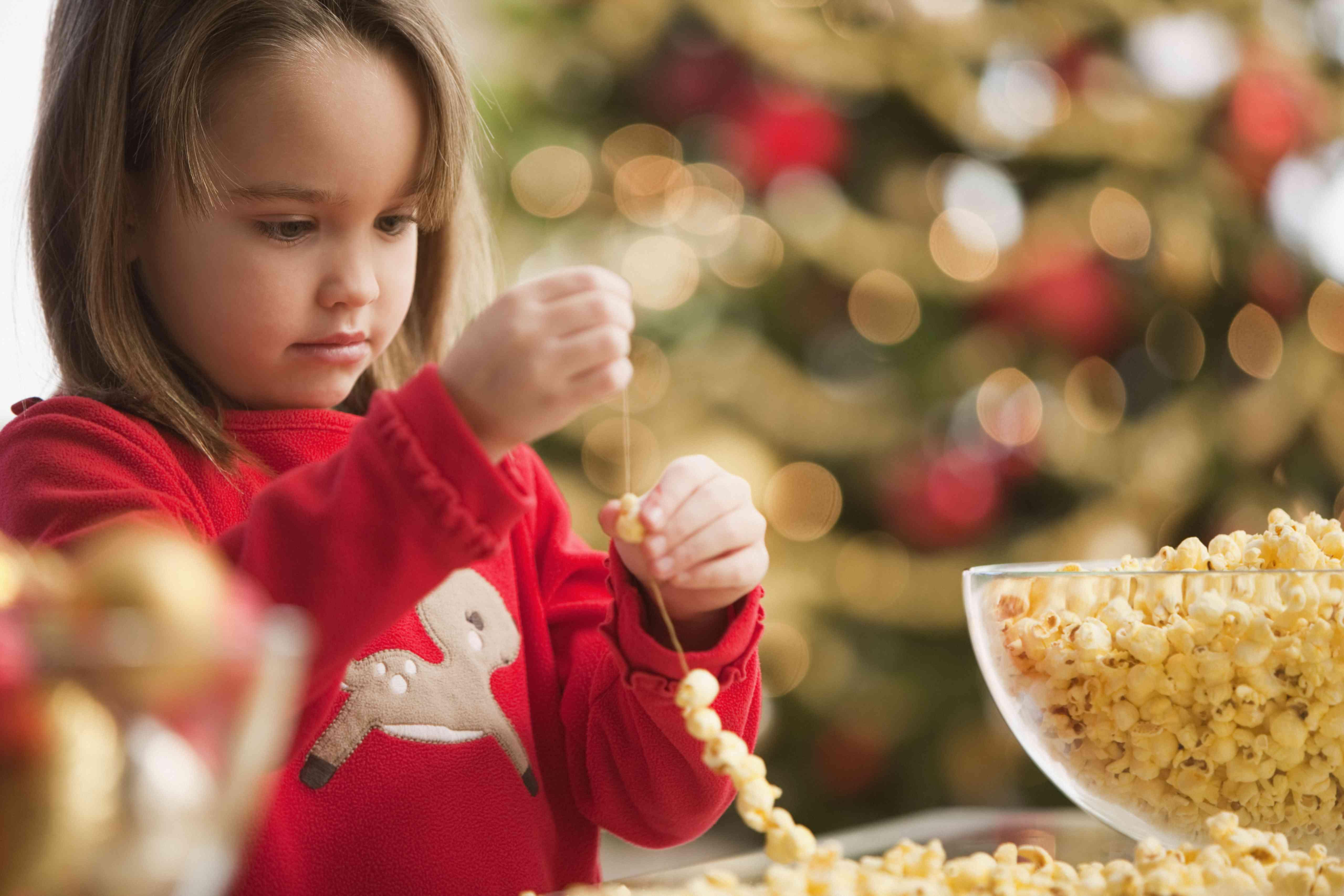 Young girl stringing popcorn at Christmastime