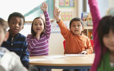 First grade classroom with children raising hands