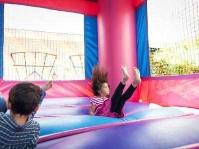Siblings playing in bouncy castle at backyard