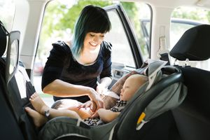 Mother fastening baby boy (12-17 months) in car seat