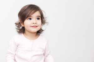 Brunette toddler girl in a pink shirt with a white background.