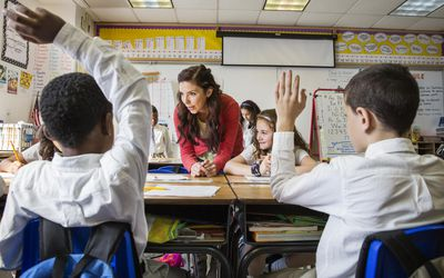 female teacher helping special education students with a project