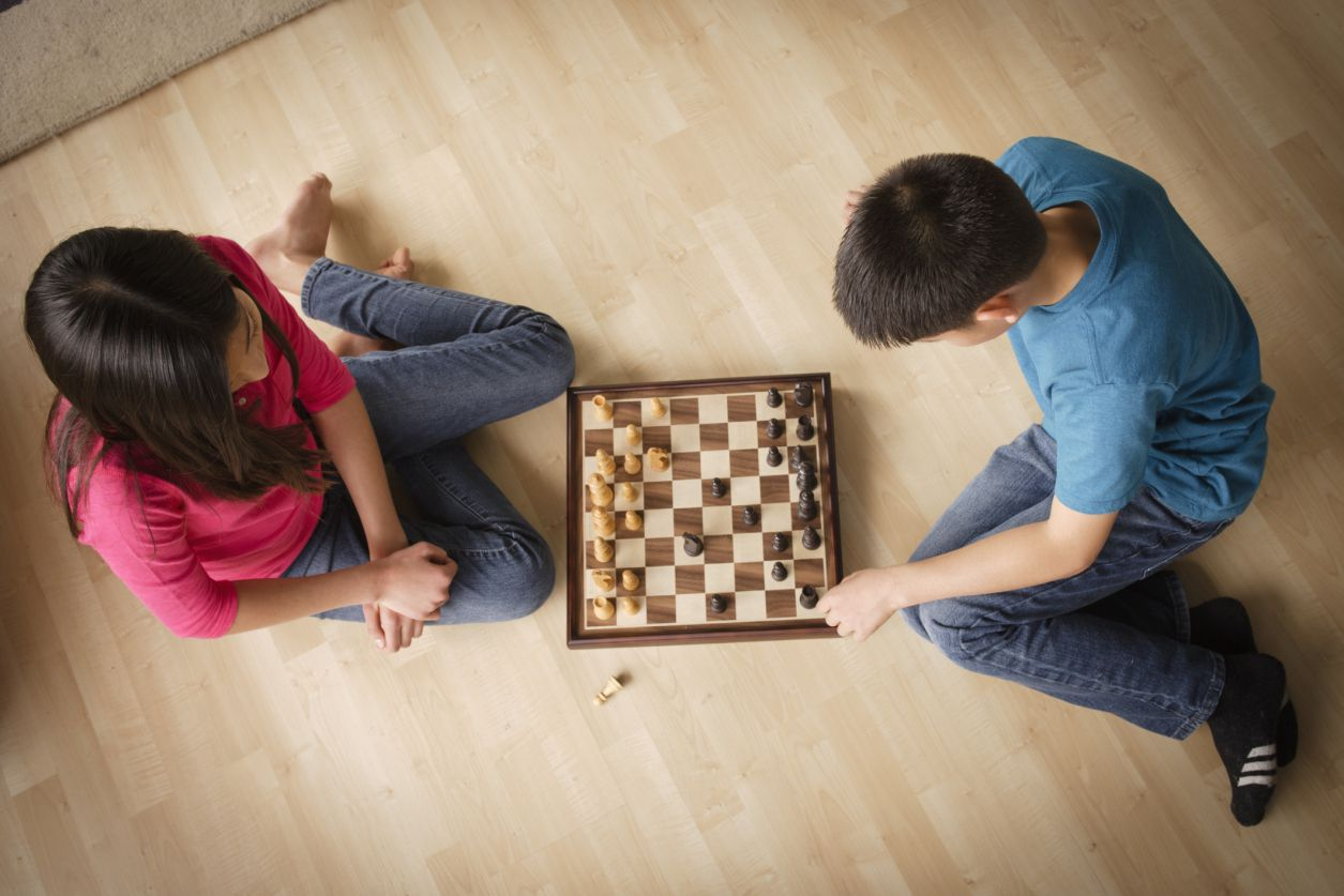 Kids playing chess on the floor