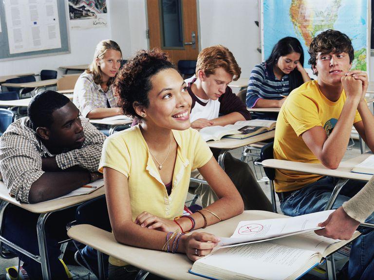 Teenage girl receiving graded homework in class, smiling