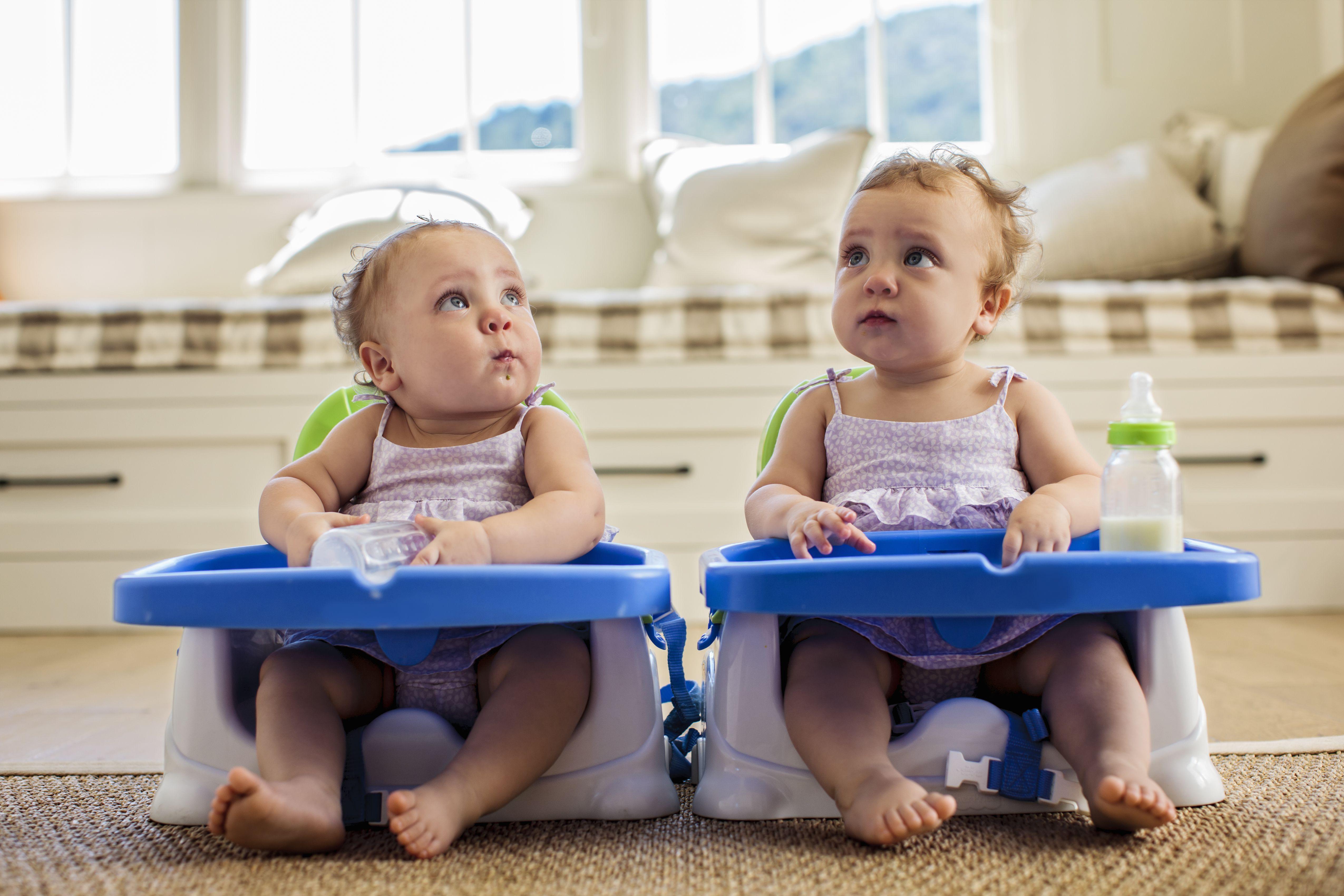 Twins sitting with milk
