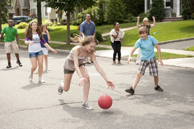 Kids playing kickball in street