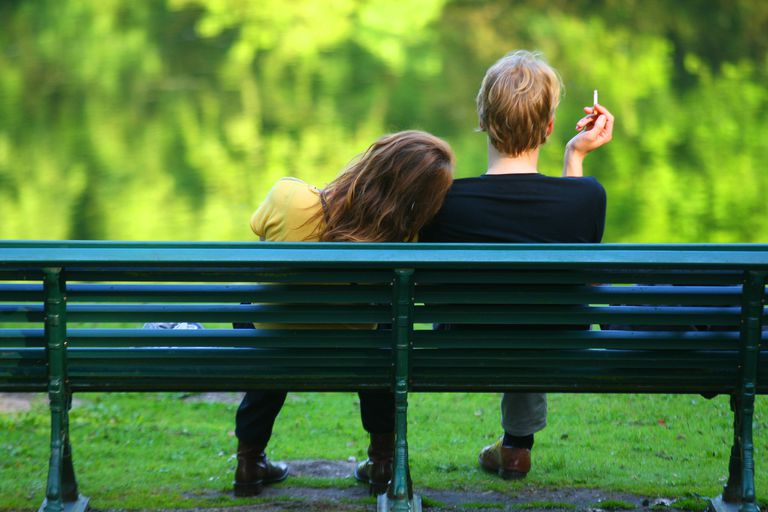 Couple sitting on a bench while male smoking nearby