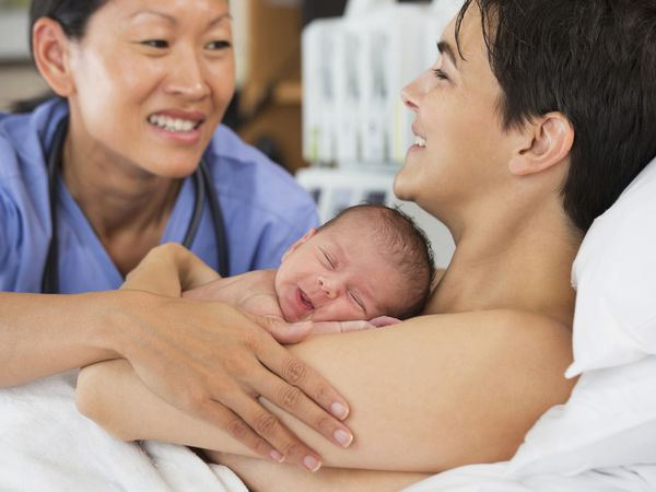 Nurse comforting mother and newborn in hospital