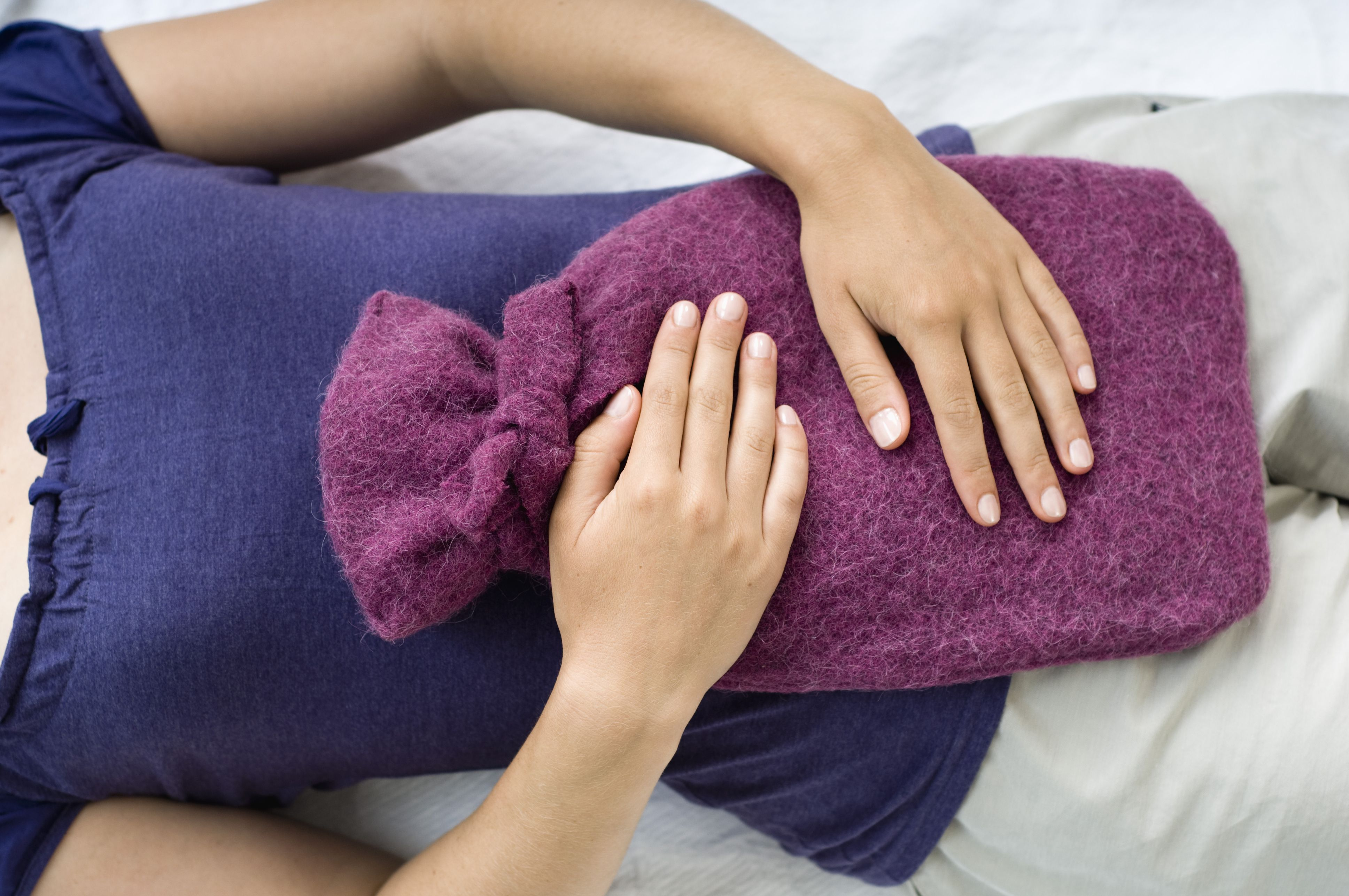 Woman with hot water bottle who has cramps from endometriosis