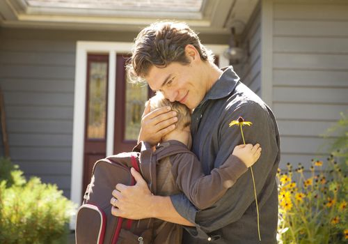 Father hugging young son wearing a backpack outside home