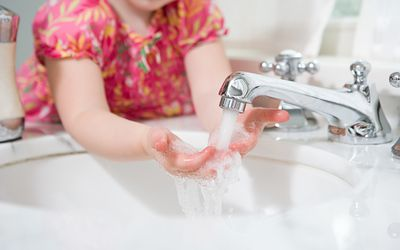 A girl washing her hands in a sink