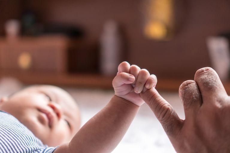 Baby grabbing parent's finger with plantar reflex
