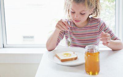 Girl (8-10) putting honey on slice of bread