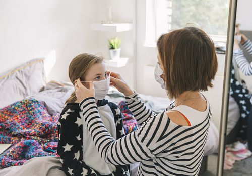 Mother putting face mask on her young daughter