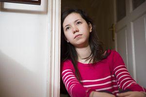 Girl leaning against doorway