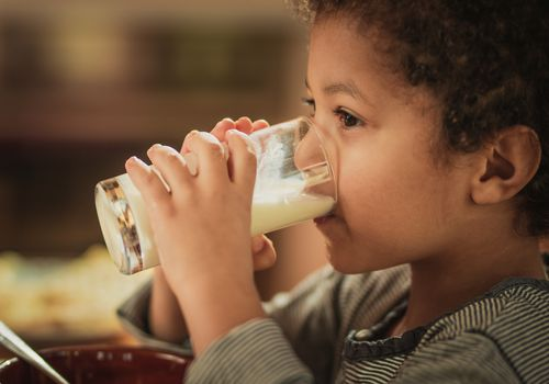 Little African American boy drinking fresh milk from a glass.