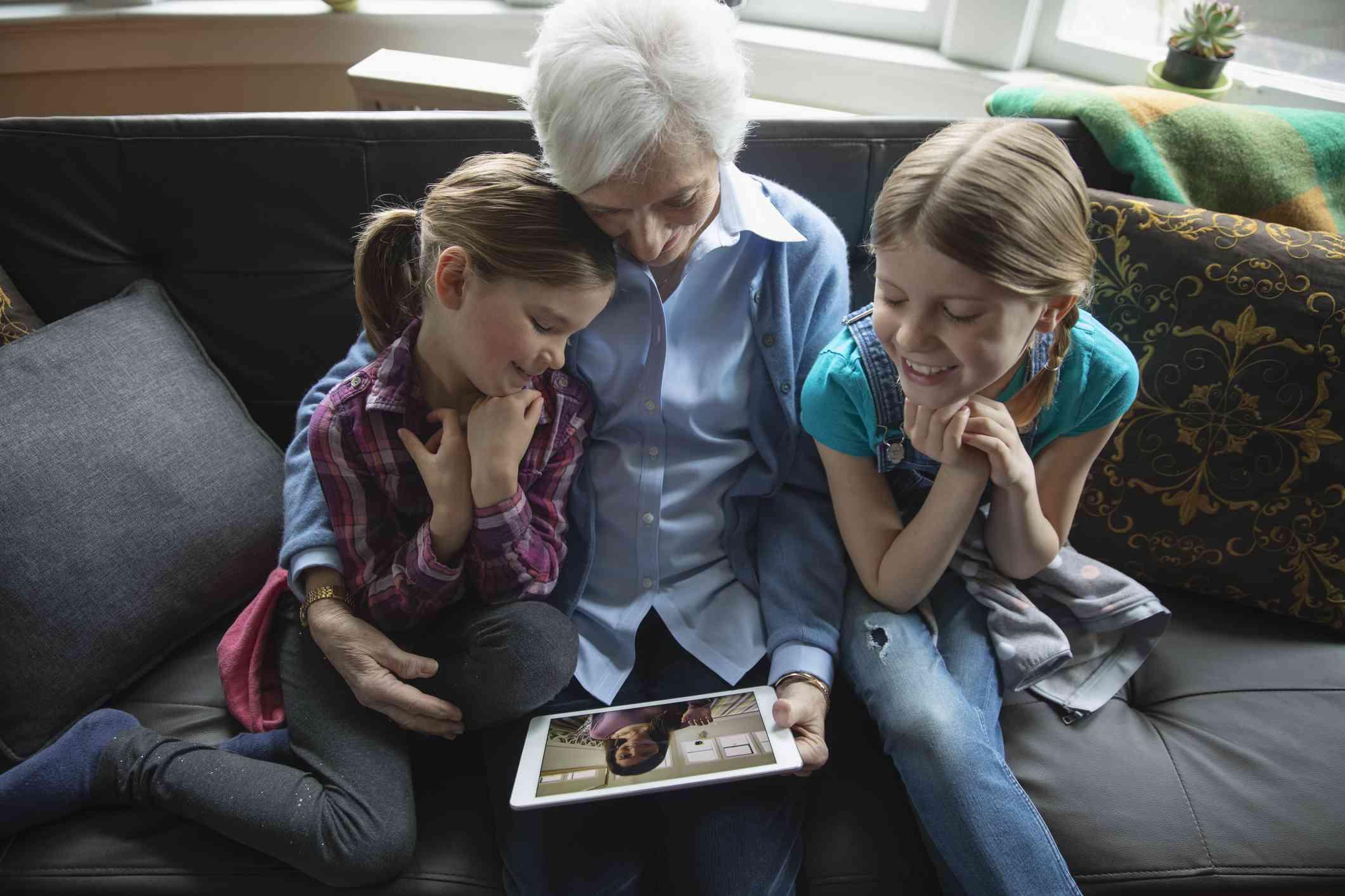 Großmutter und Enkel Video mit digitaler Tablette auf dem Sofa im Chat