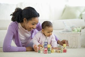 Woman playing with blocks with baby