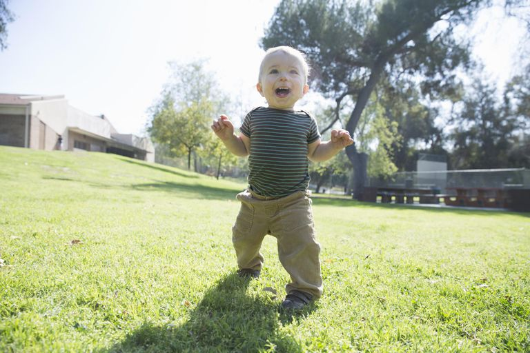 Baby boy learning to walk on grass