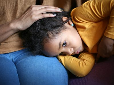 upset girl with head on mother's lap