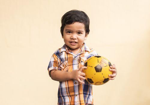 Toddler boy holding a ball