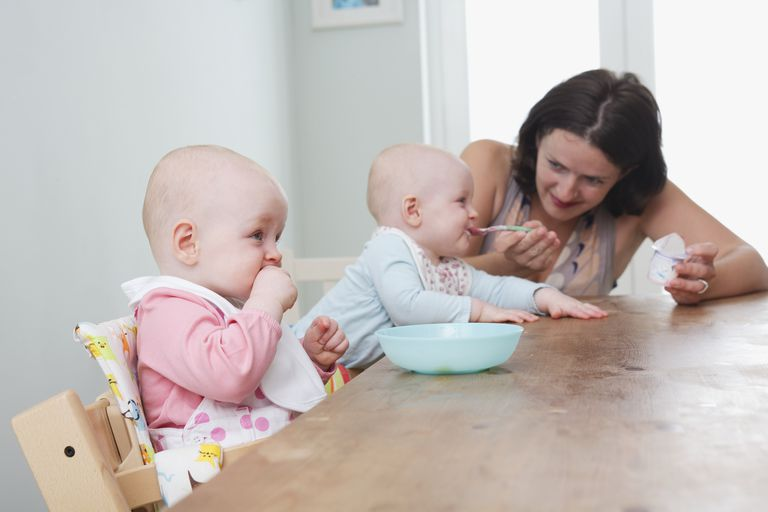Twin baby girls seated at table, one being spoon-fed, the other girl chewing on her fist