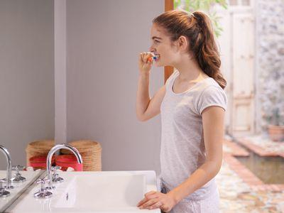 Teen girl brushing her teeth