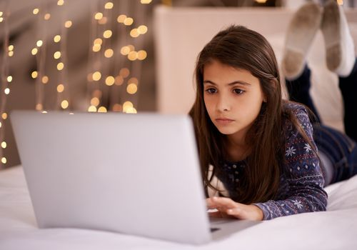 Tween girl using a laptop on her bed