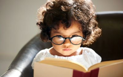 Little girl wearing glasses and reading a book