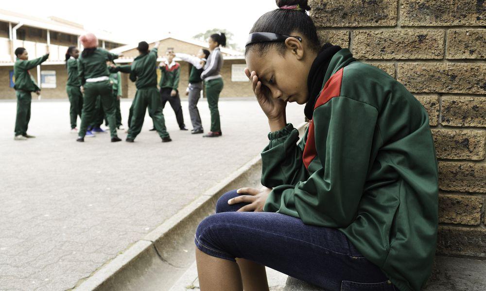 Upset girl sitting in school yard