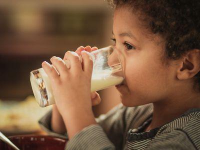 Little African American boy drinking fresh milk from a glass.