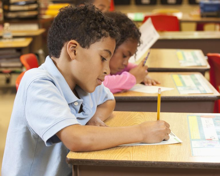 Mixed race student studying at desk in classroom