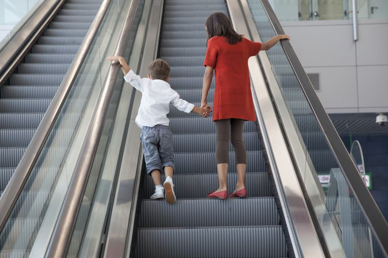 Boy and girl standing on escalator.