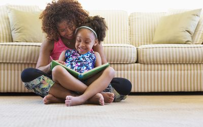 Mixed race mother and daughter reading book on floor near sofa