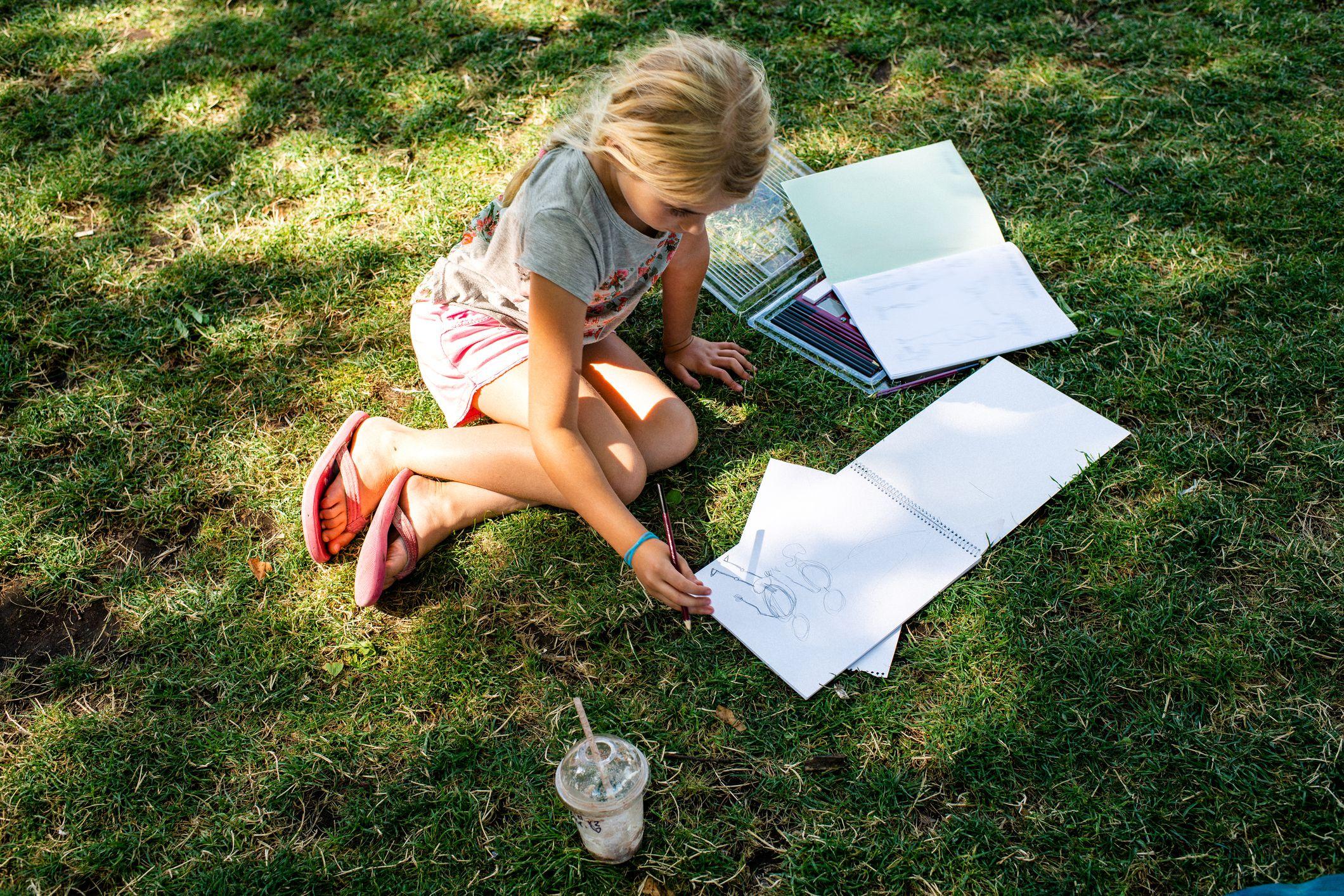 Little girl doing homework on the grass