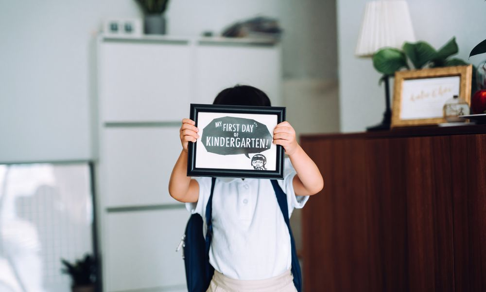kid holding first day of kindergarten sign