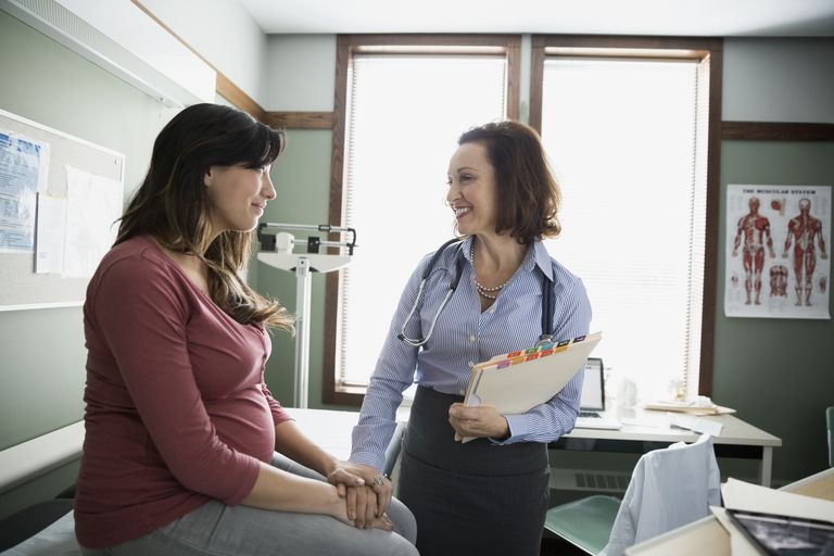 Caring doctor talking to pregnant woman
