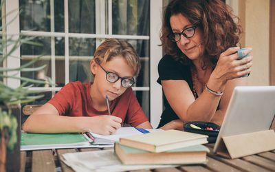 Young student doing homework at home with school books newspaper, digital pad helped by his mother. Mum control, help and teaching his son. Education, family, lifestyle and homeschooling concept.