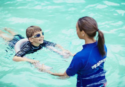 Young boy learning to swim in pool with teacher